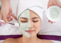 Beautician applying clay face mask on face of pretty woman